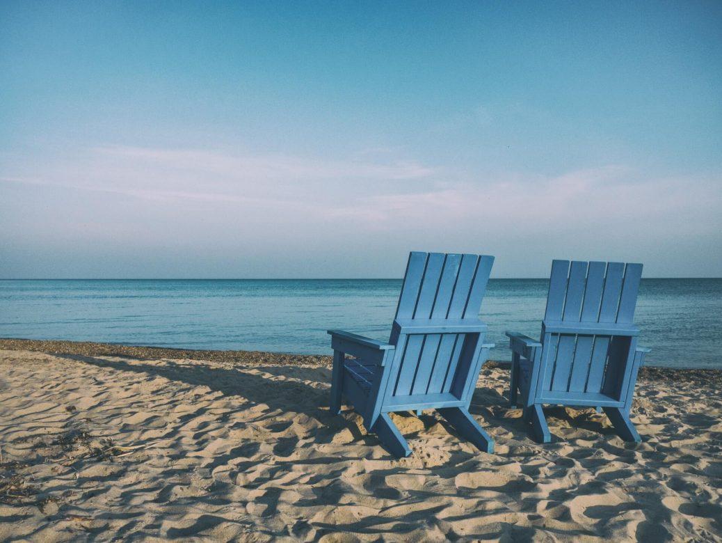 Zwei Stühle am Strand eines fiktiven Urlaubsorts