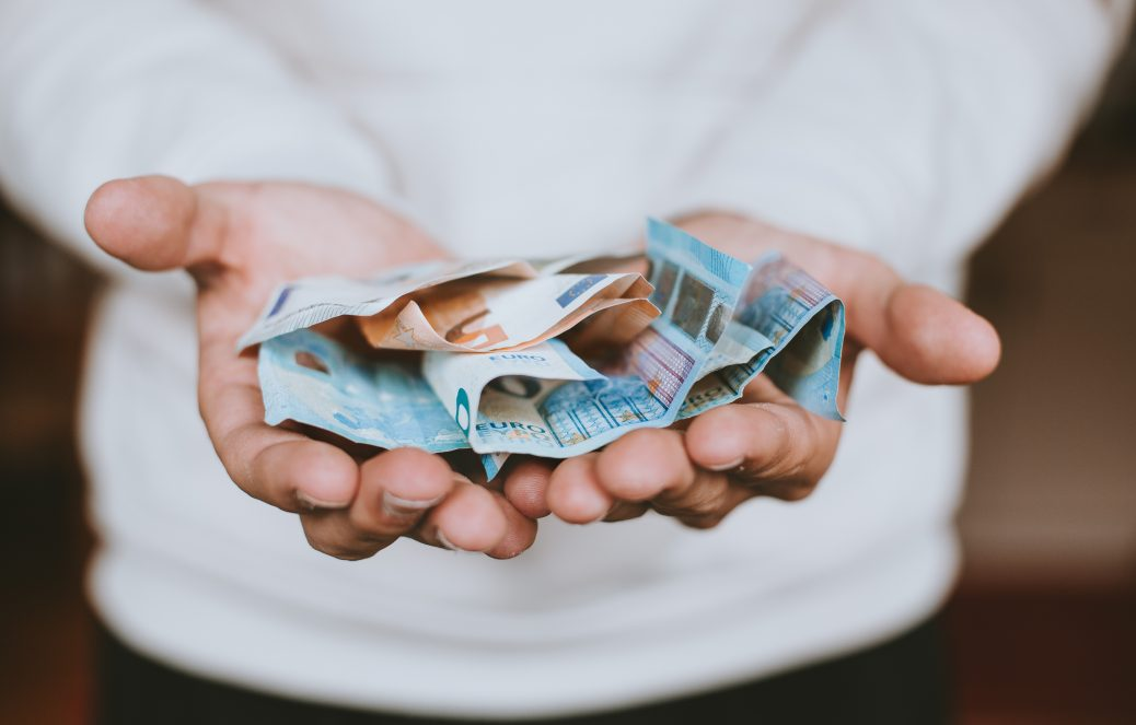 Several euro banknotes in the hands of an unknown person