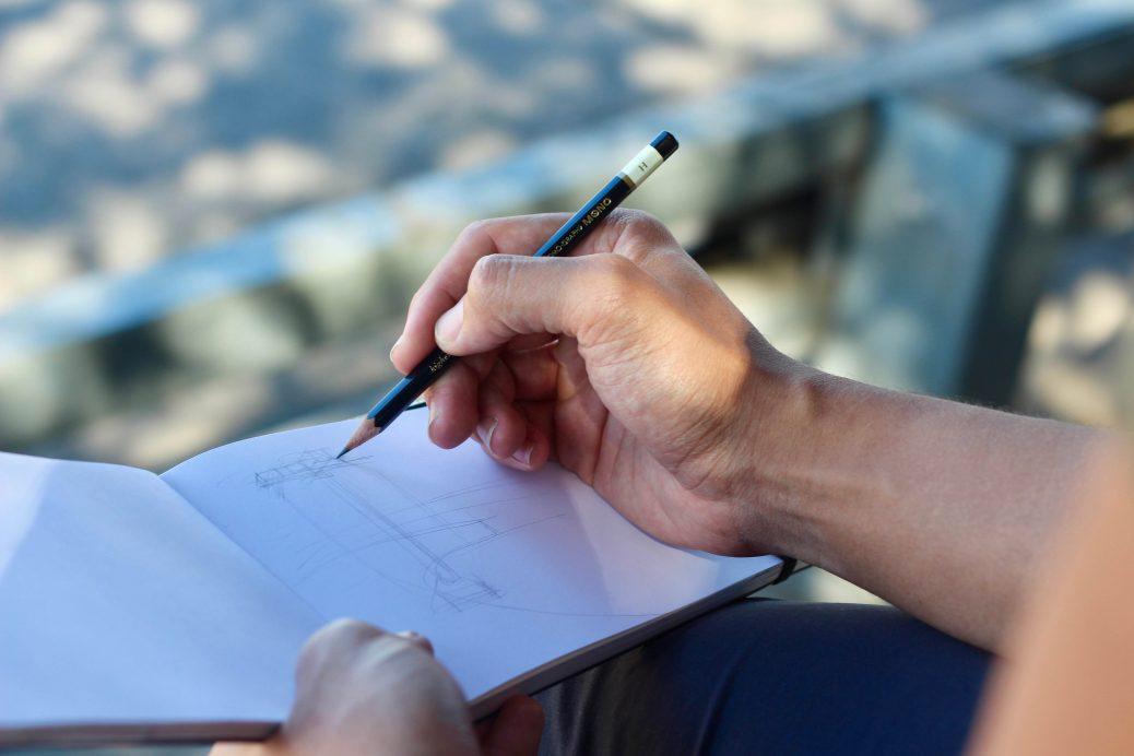 Eine unbekannte Person zeichnet mit Bleistift in ein Notizbuch
