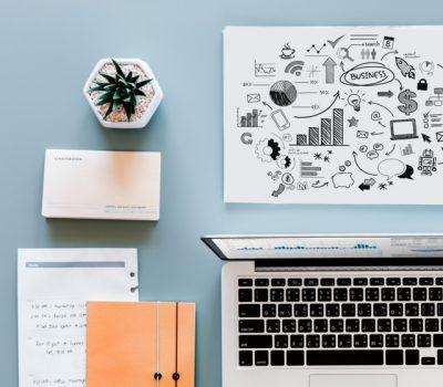 Ein aufgeräumter Schreibtisch mit Businessplan und MacBook