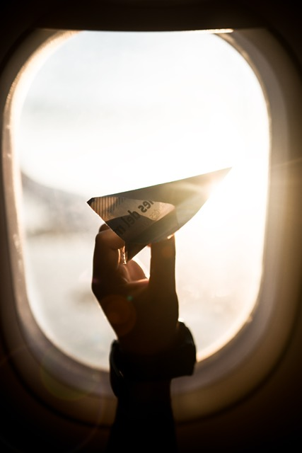 A paper airplane in the hands of a child in front of the window of a passenger airplane